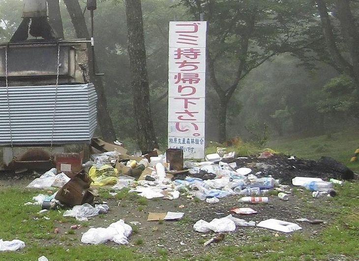 ごみの持ち帰りを呼びかける看板の下に散乱するごみ=兵庫県猪名川町(同町提供)