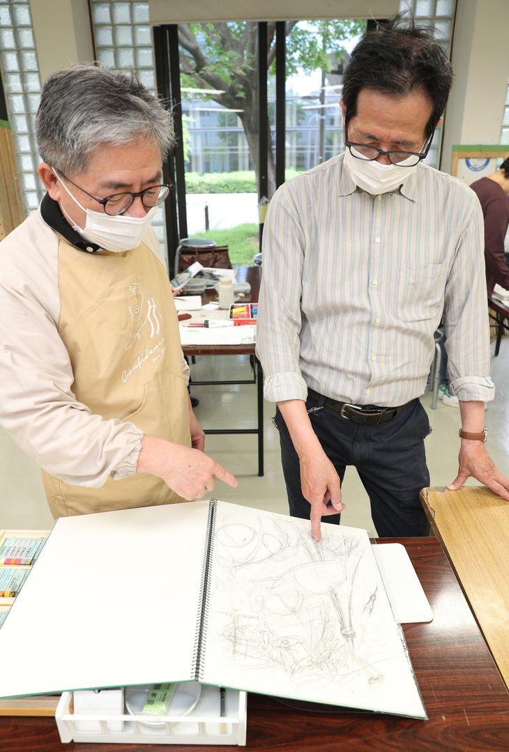 田伏勉先生(右)にスケッチブックに描いたラフ画を見せる記者(寺口純平撮影)