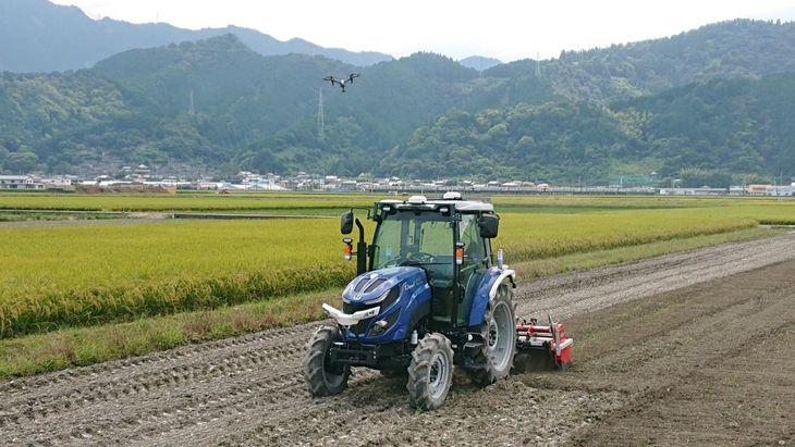 農地を走る自動運転トラクターとドローン(愛媛県西条市提供)