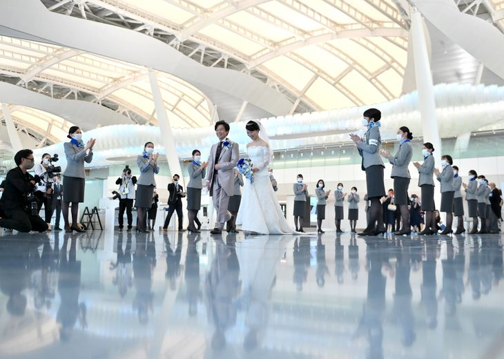 コロナ禍で減便が続く国際線の旅客機で結婚式のサービスが始まった。新郎新婦は国際線出発ロビーで参列者やスタッフに迎えられた =羽田空港(宮崎瑞穂撮影)