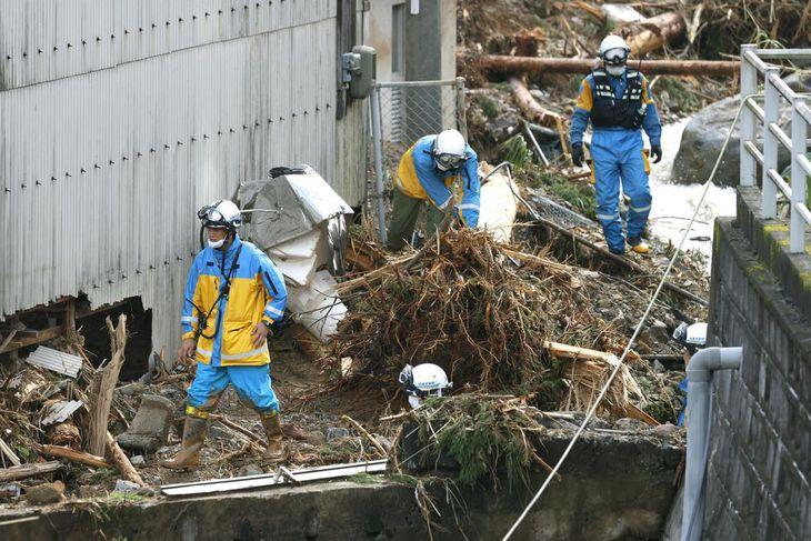 熊本県津奈木町の土砂崩れ現場近くで行方不明者の捜索をする警察官=8日午前8時40分