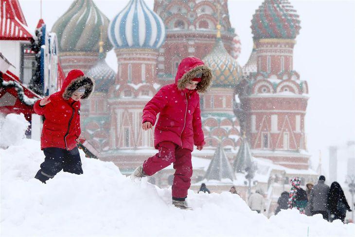 モスクワで雪の中を歩く子どもたち=13日(タス=共同)