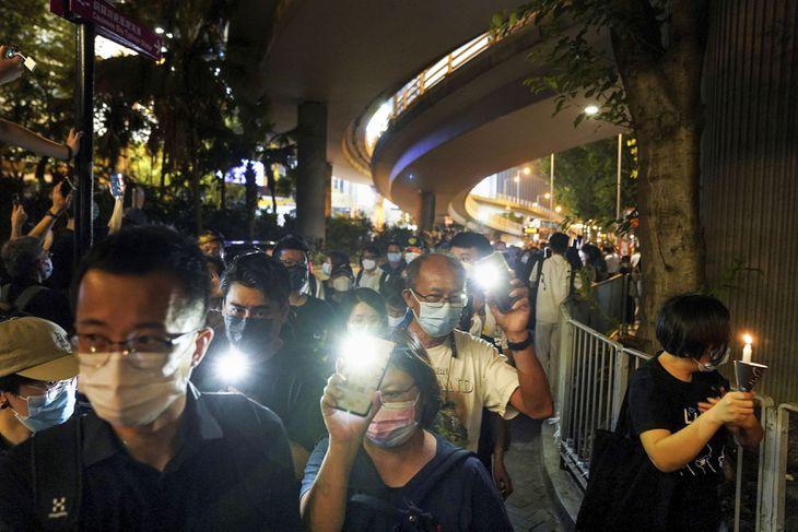 天安門事件から32年の4日、香港中心部のビクトリア公園周辺でライトをつけたスマートフォンやろうそくを手に歩く人たち(ロイター)