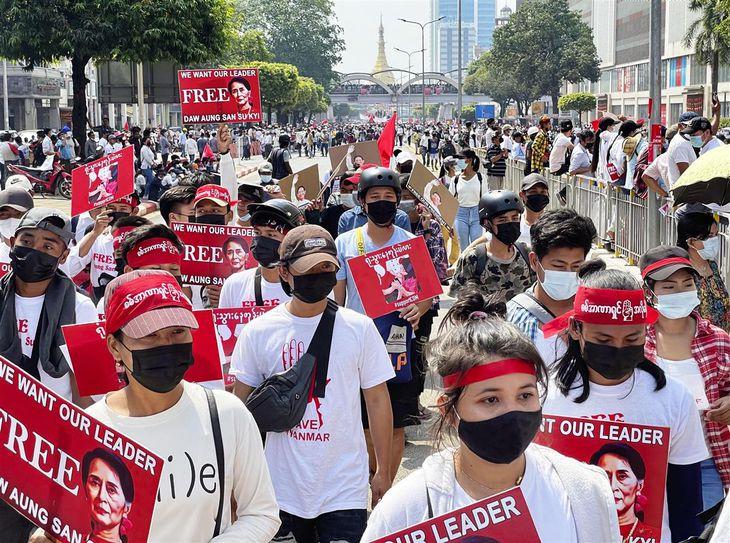 22日、ミャンマー・ヤンゴンで、クーデターに抗議し行進するデモ参加者(共同)