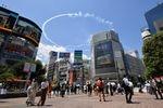 【東京五輪2020】23日の開会式を前に予行飛行し、国立競技場上空に五輪の輪を描いたブルーインパルス。円の一部が渋谷スクランブル交差点でも見られた=21日午後、東京都渋谷区(大西史朗撮影)