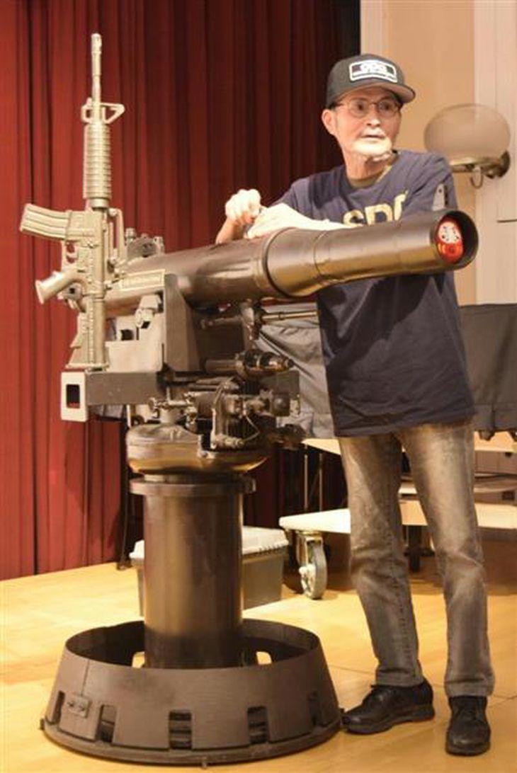 自ら制作した作品の大砲でロドニー賞受賞の祝砲を上げる榎忠さん=神戸市中央区