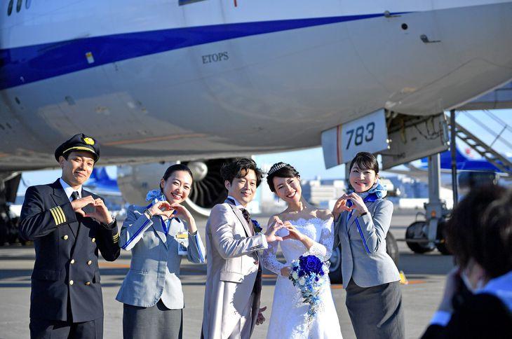 全日空は運航便が減少した国際線を利用し、旅客機や出発ロビーを会場にした結婚式のサービスを始めた。当日は機長や客室乗務員など100人のスタッフが運営。新郎の村上徹さん(中央)は「普段経験できない機内での挙式など、飛行機好きにとって夢のようだった」と話した =羽田空港