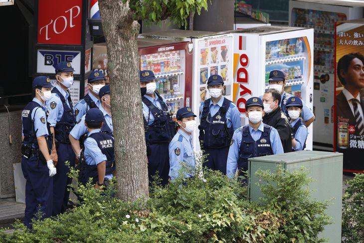 男が女性店員を人質に立てこもったインターネットカフェが入るビルの前で警戒する警察官=18日午前8時50分、さいたま市