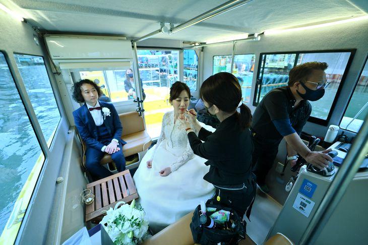 船上で結婚写真のためメイク直しをする新婦。「東京ウォータータクシー」で東京湾や隅田川、日本橋をまわり撮影するサービスが今年3月に始まった =都内(宮崎瑞穂撮影)