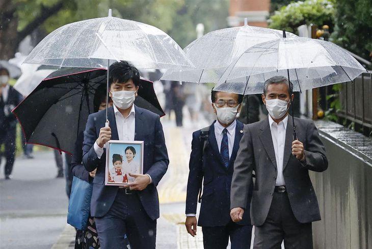 妻の真菜さんと長女の莉子ちゃんの写真を手に東京地裁に向かう松永拓也さん(前列左)ら=8日午前8時50分、東京・霞が関