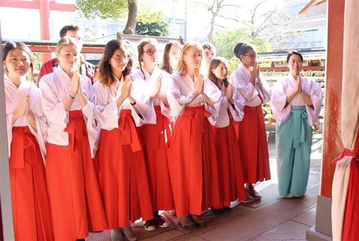 巫女装束で神社でのマナーを学ぶ留学生ら。右は宮司の太田垣さん